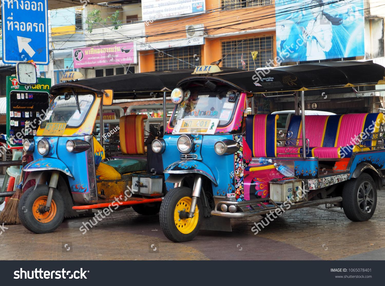 PAKKRET, NONTHABURI, THAILAND - APRIL 6, 2018: Two three-wheelers locally called tuk-tuk are parked outside a local market on April 6, 2018 in Pakkret, Nonthaburi, Thailand.