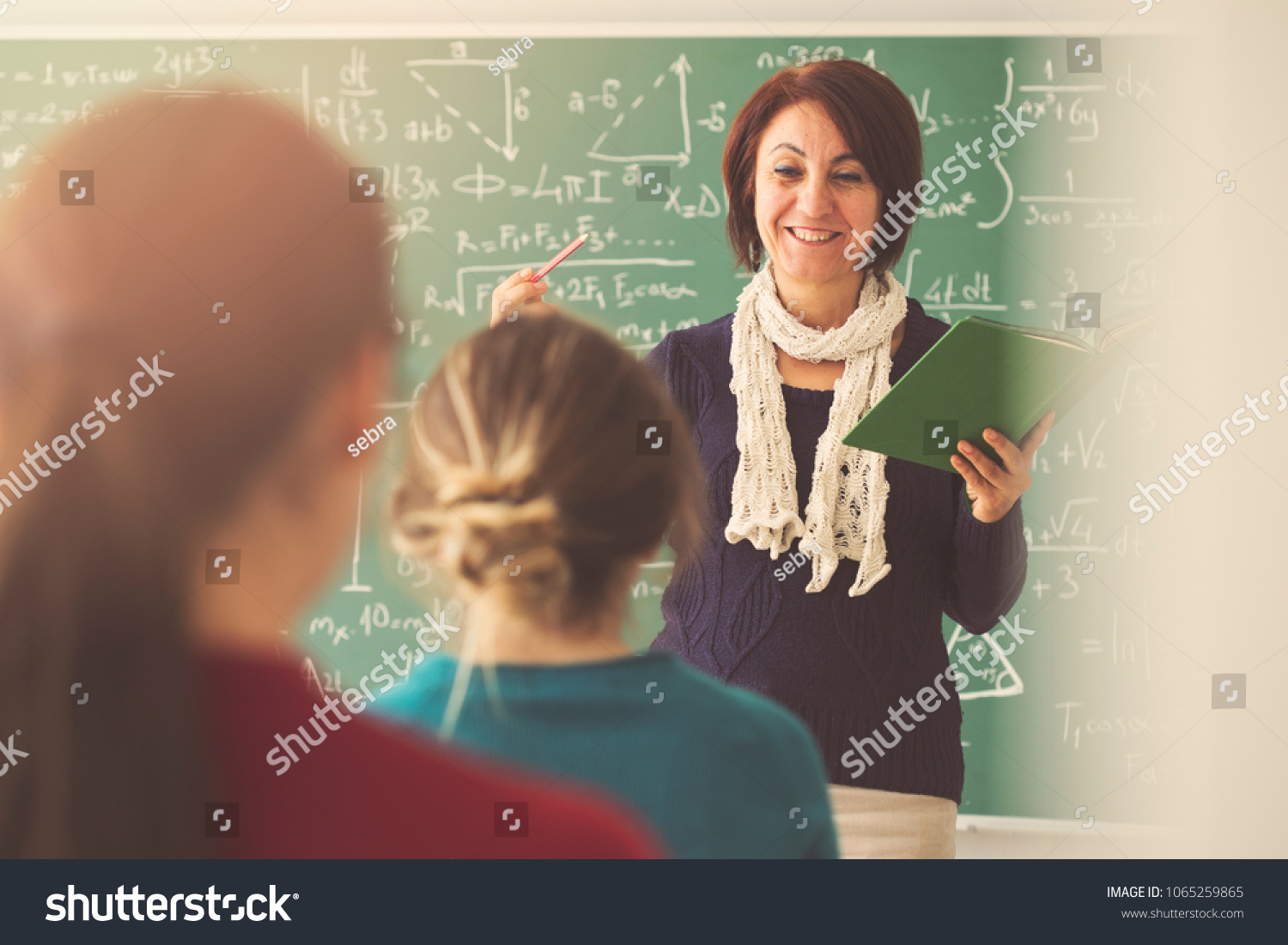 Teacher giving lesson to students in classroom #1065259865
