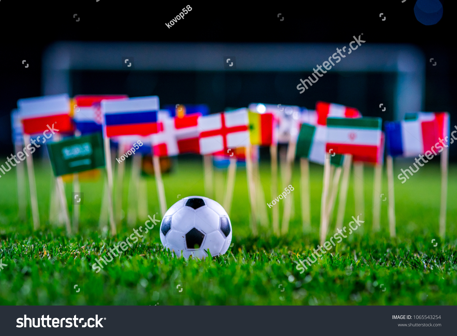 Football ball on green grass and all national flags #1065543254 - 123PhotoFree.com