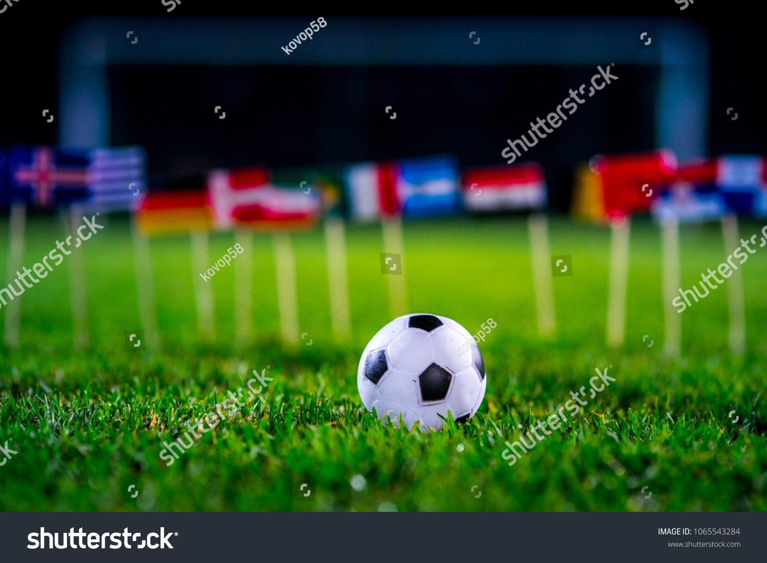 Football ball on green grass and all national flags #1065543284