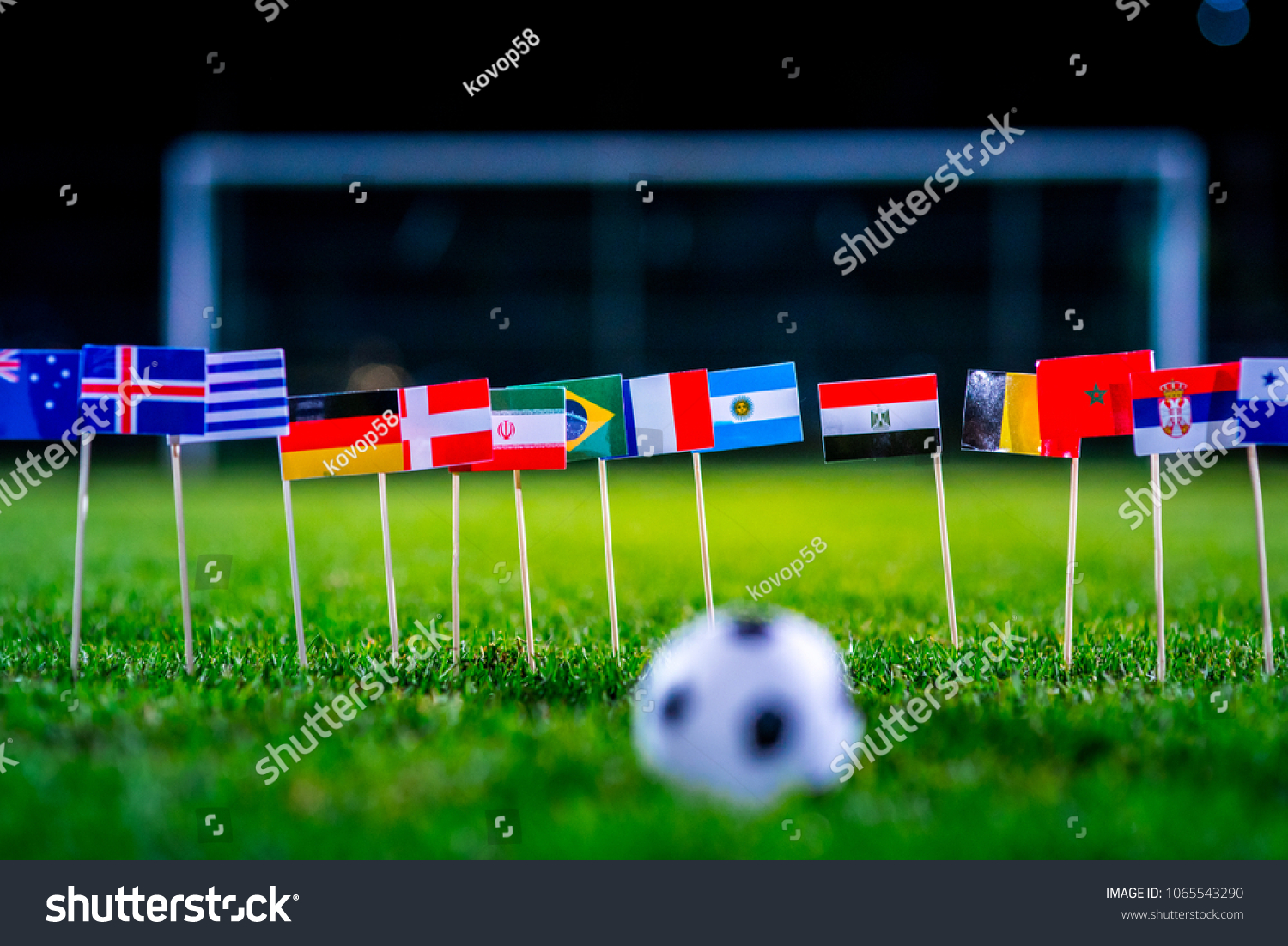 Football ball on green grass and all national flags  #1065543290