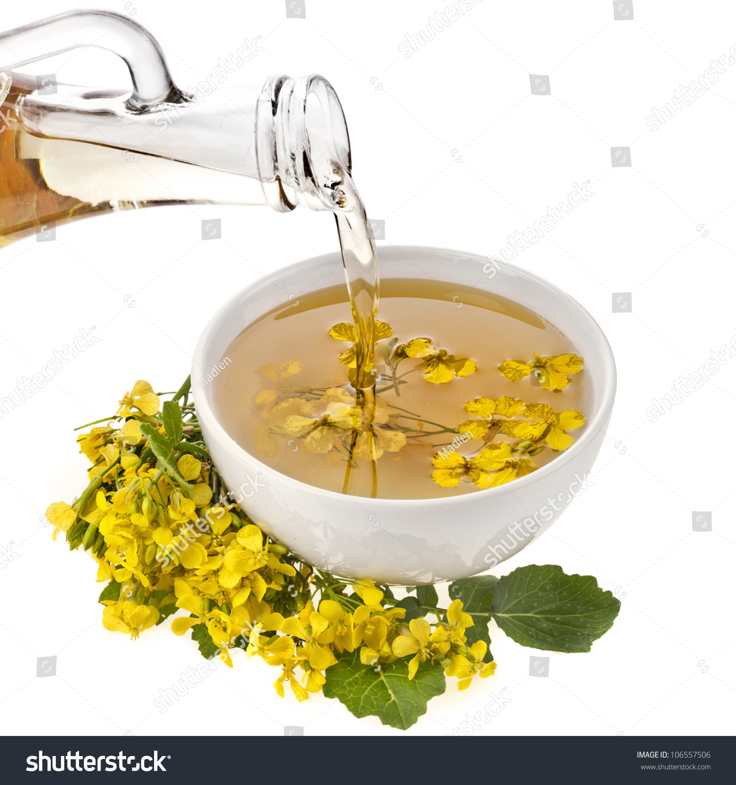 Mustard Oil Pour In A Bowl With Mustard Flower Bloom Isolated White Stock