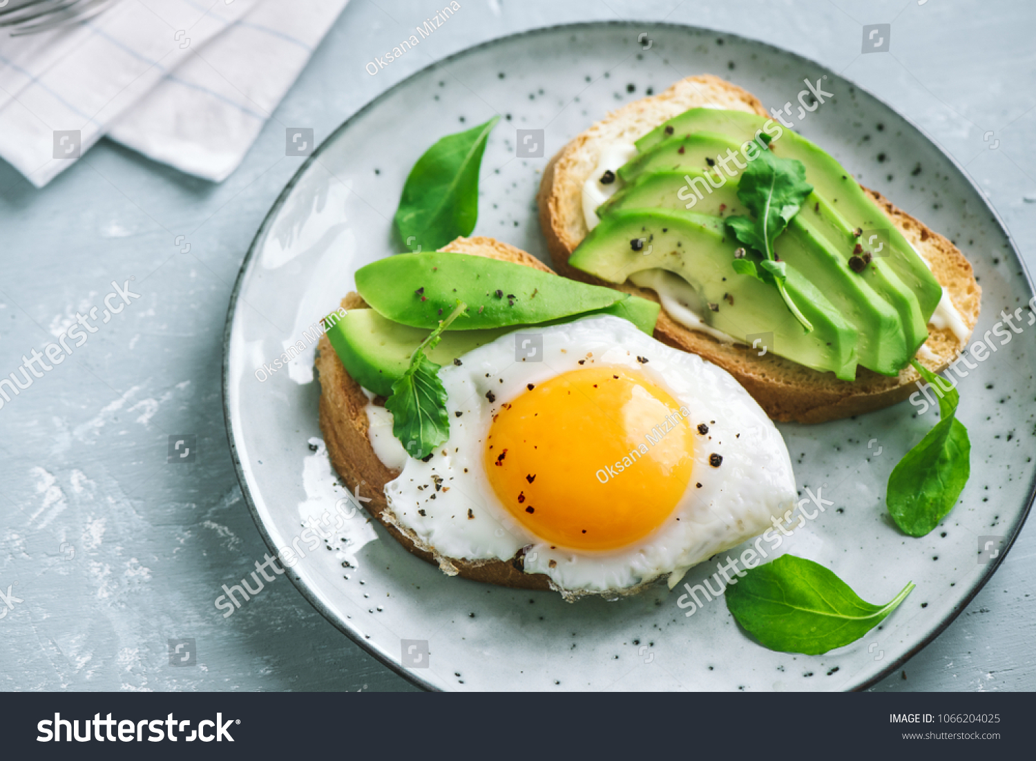 Avocado Sandwich with Fried Egg - sliced avocado and  egg on toasted bread with arugula for healthy breakfast or snack. #1066204025
