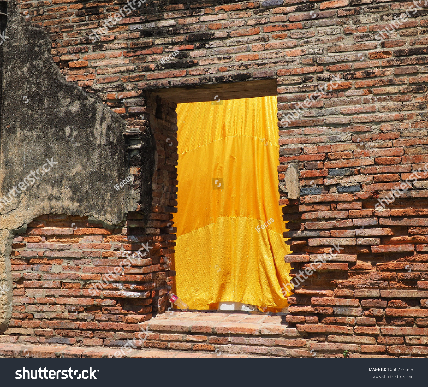 A yellow textile fabric hangs in a weathered brick wall frame