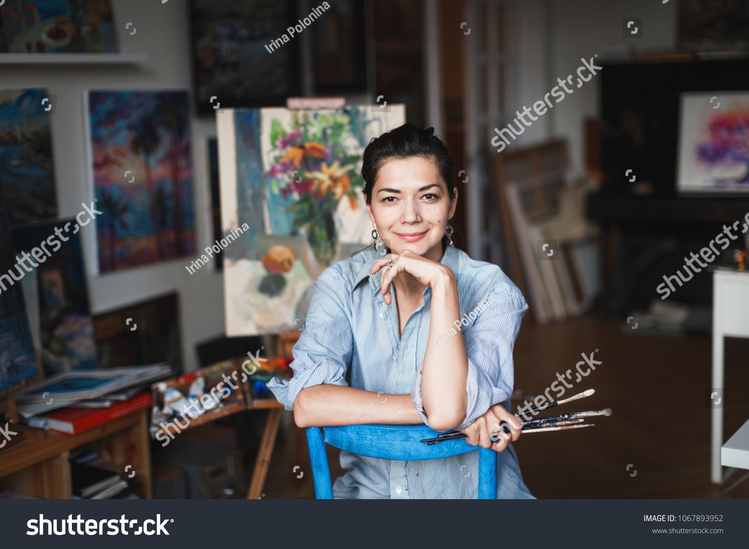 A young smiling brunette woman artist in her Studio is holding a brush. Near her easel, paintings and various art equipment. #1067893952