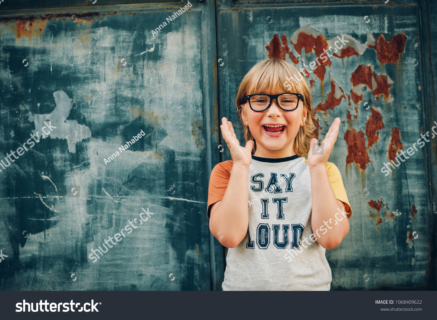 1c52c90cf83a Outdoor portrait of funny little boy wearing glasses and t-shirt with sign