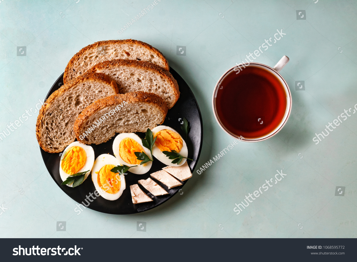 Healthy breakfast. Boiled eggs, bread, butter, greens and tea #1068595772