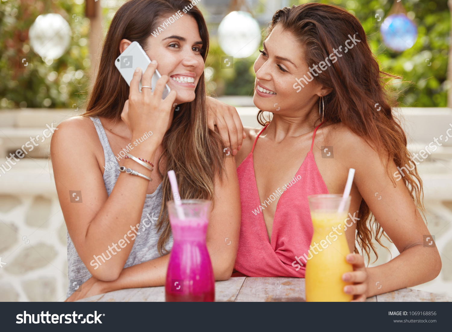 Horizontal shot of pretty young female lesbians recreat at outdoor cozy  cafe: gorgeous brunette woman