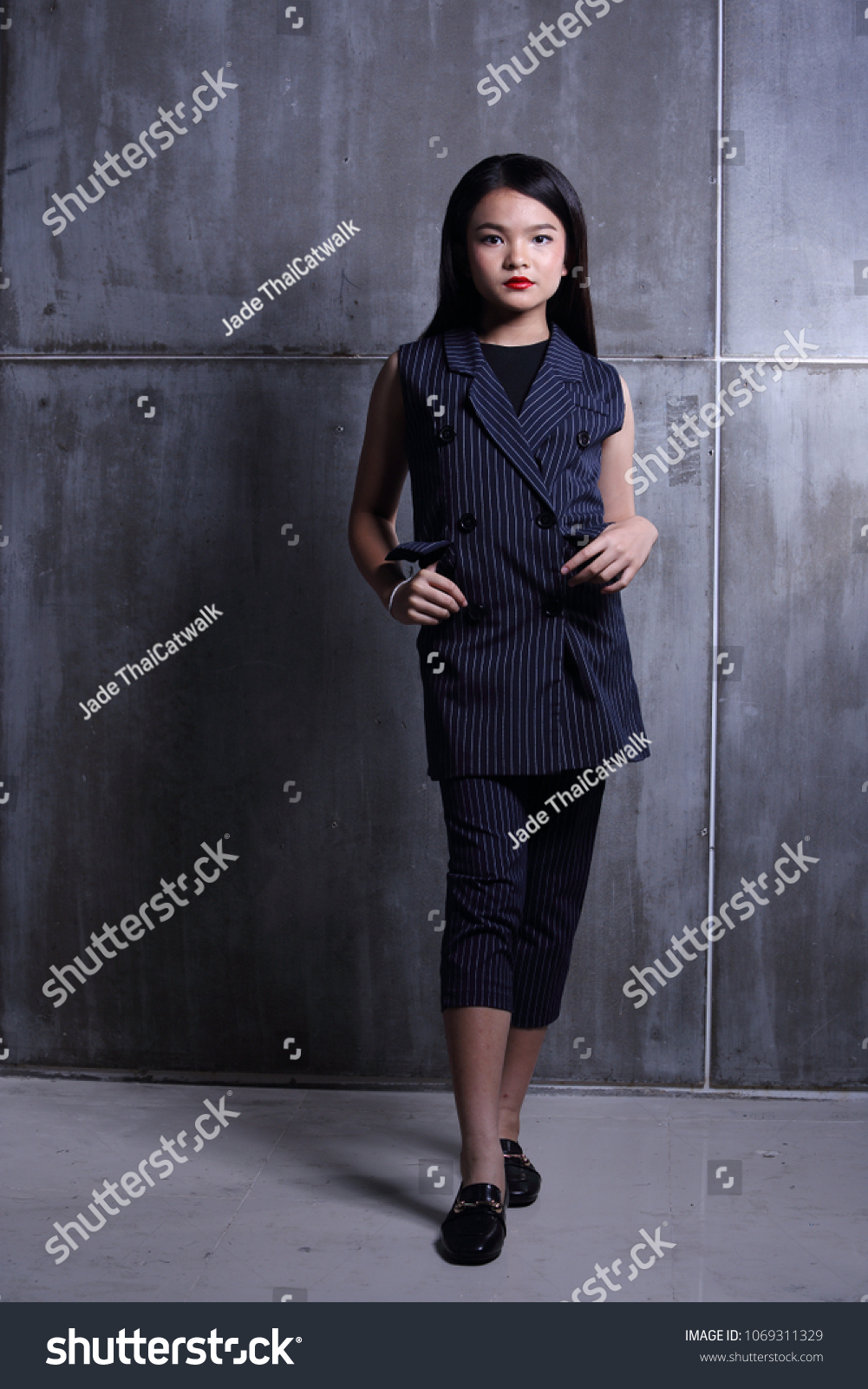 Business Kid Girl in formal suit stand on dark abstract background, studio lighting copy space for text logo, black hair eleven years old full length snap body #1069311329