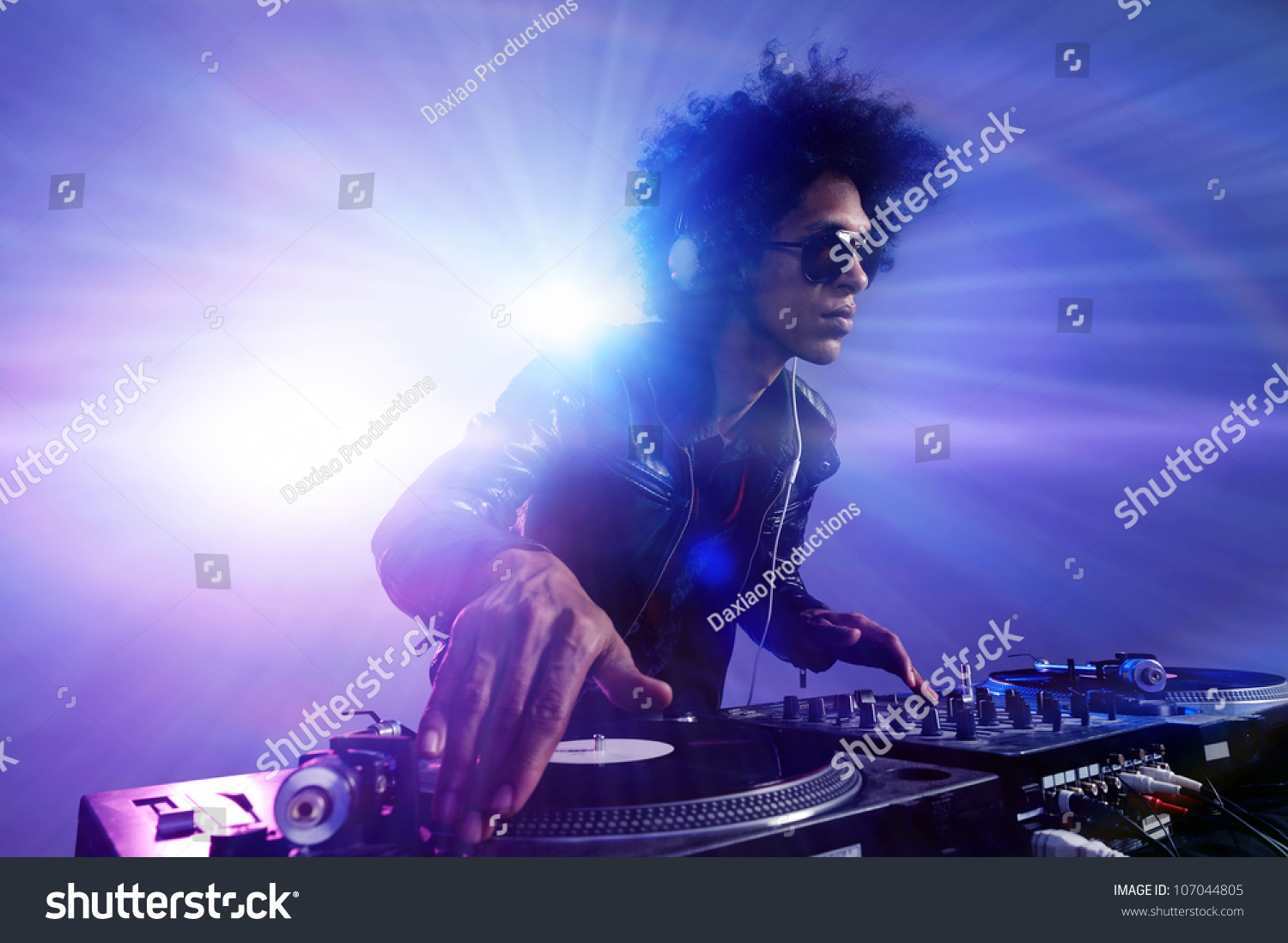 Club DJ with afro hairstyle playing mixing music on vinyl turntable at party wearing sunglasses with lens flare from nightlife lights. #107044805