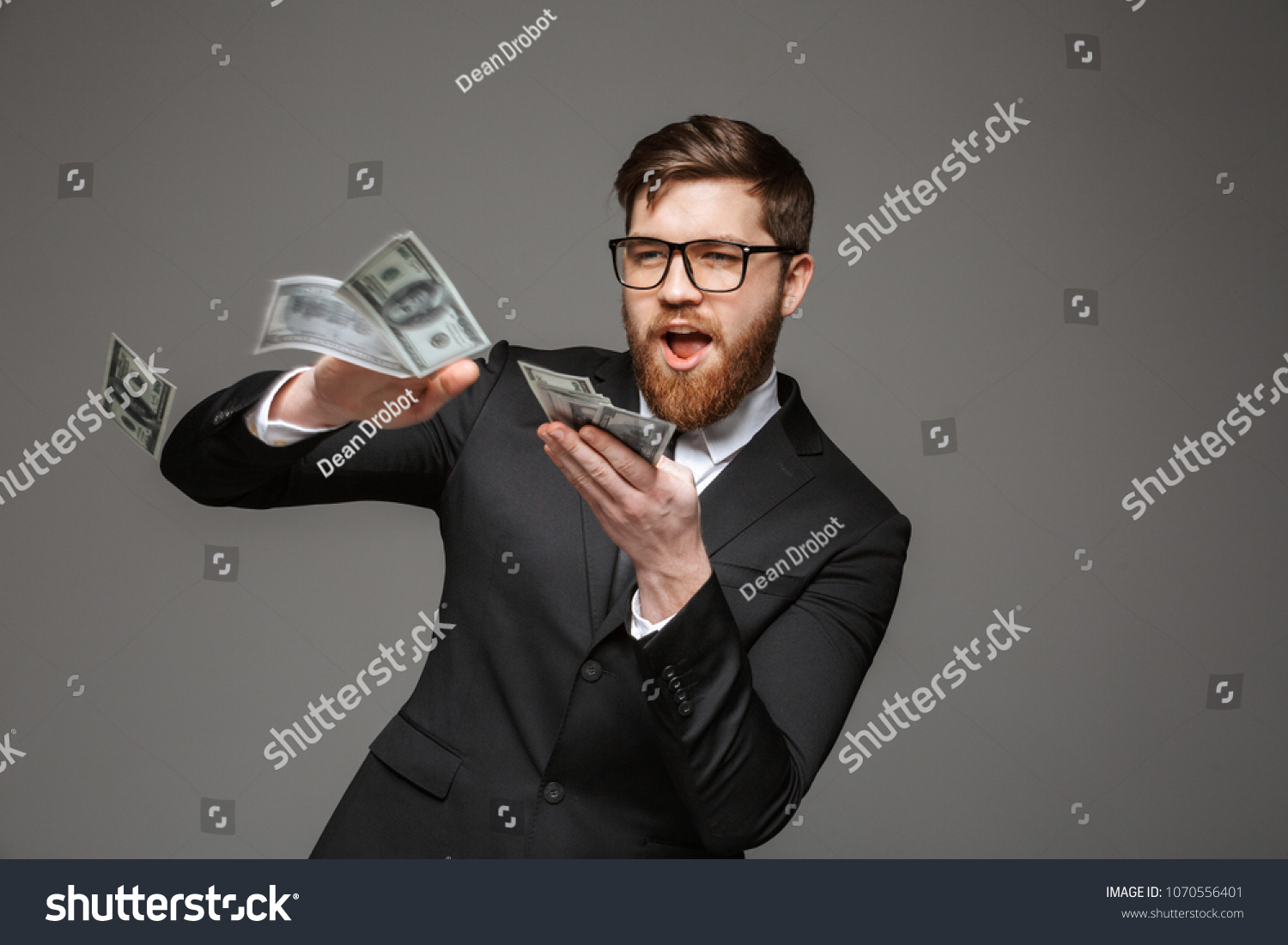 Portrait of a happy young businessman throwing out money banknotes isolated over gray background #1070556401