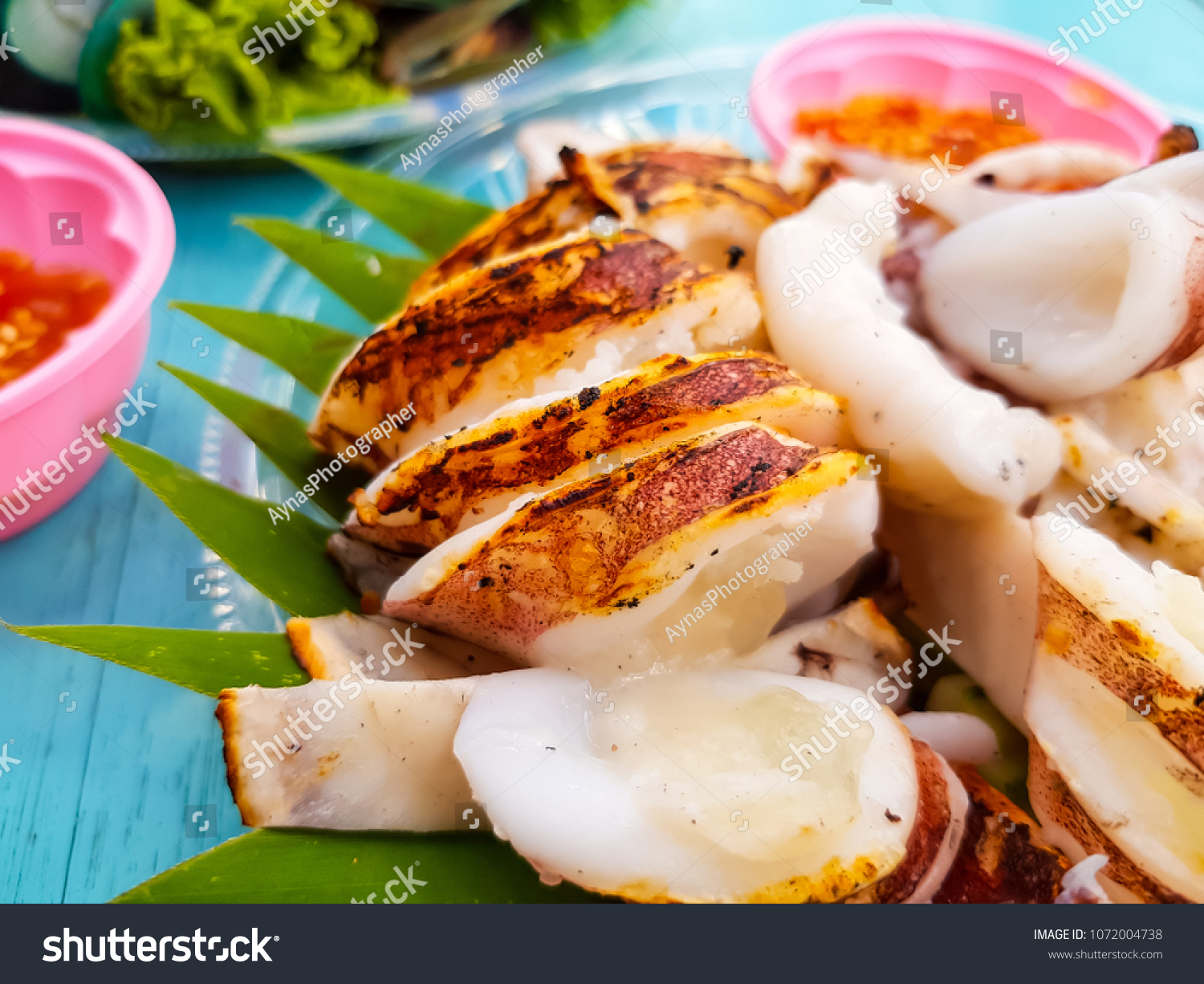 Thai street foods at Pattaya, Thailand. Grilled squid and Thai spicy chilli  sauce in