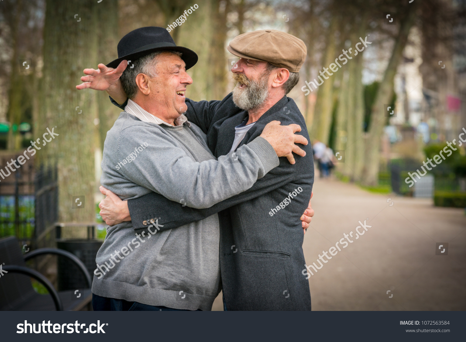 Two old friends in hats meet and hug each other in a park in Malmo Sweden