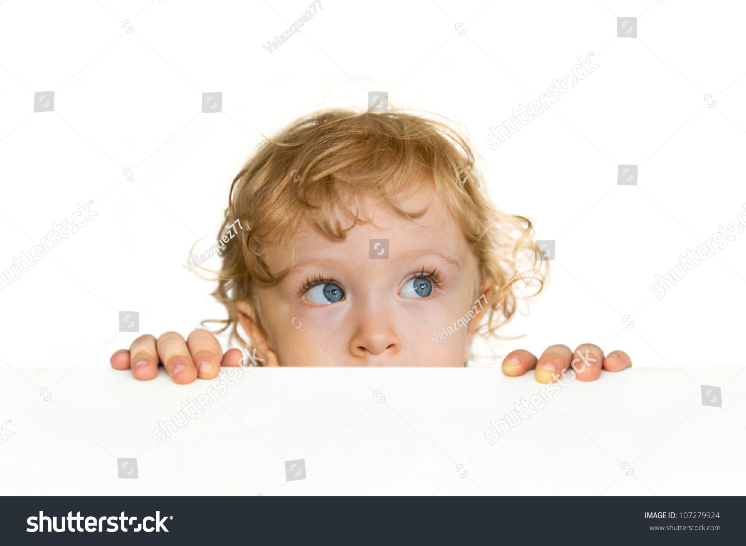 Curious Cute Child Looking Over Table Stock Photo