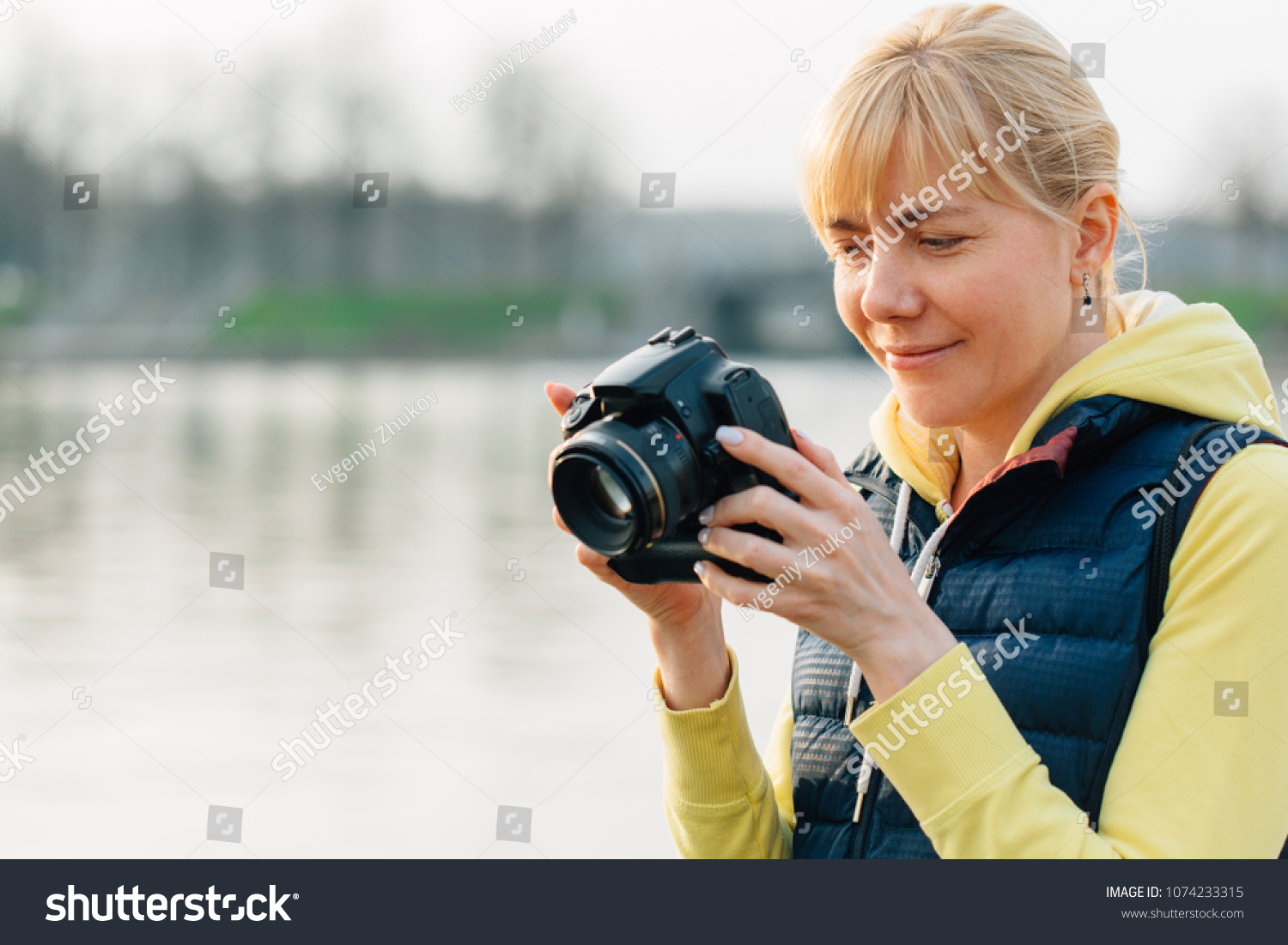 Girl with professional camera in hands. Close up of female photographer in  park. Pretty