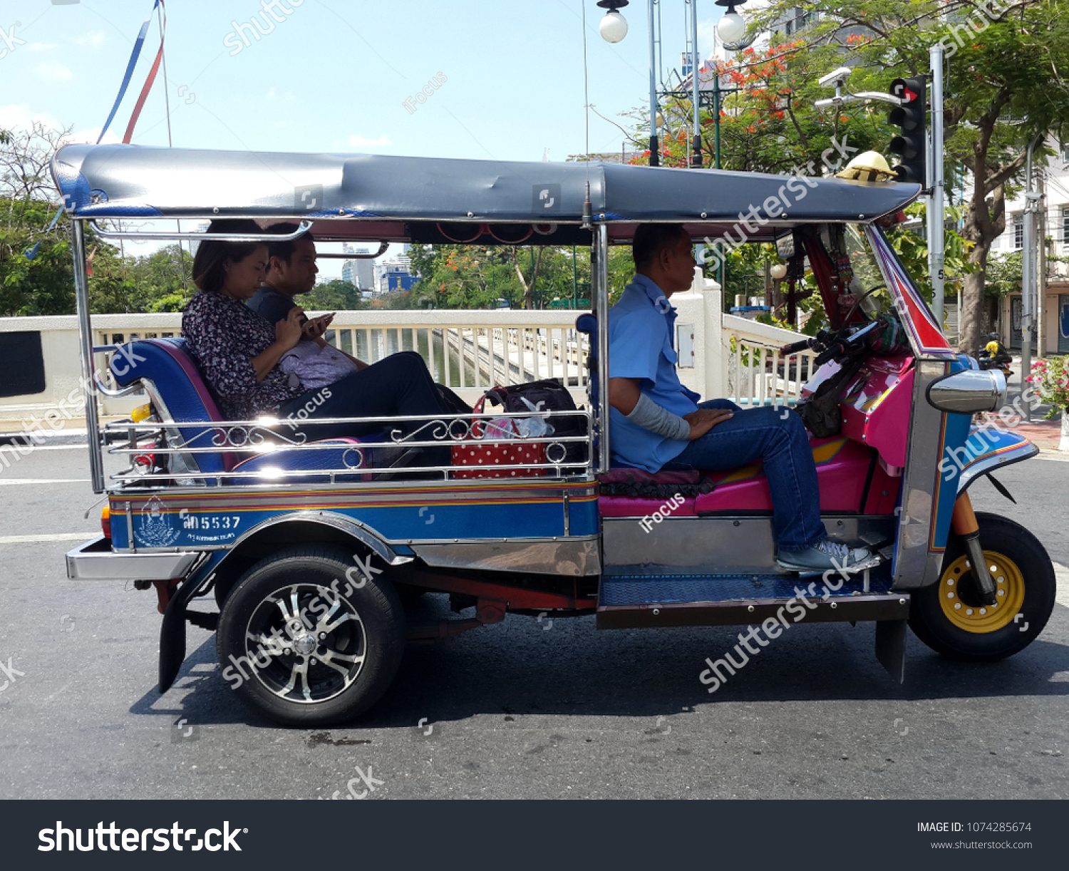 BANGKOK, THAILAND - APRIL 22, 2018: A couple sits in a popular type of transportation locally known as tuk tuk on April 22, 2018 in Thai capital Bangkok.