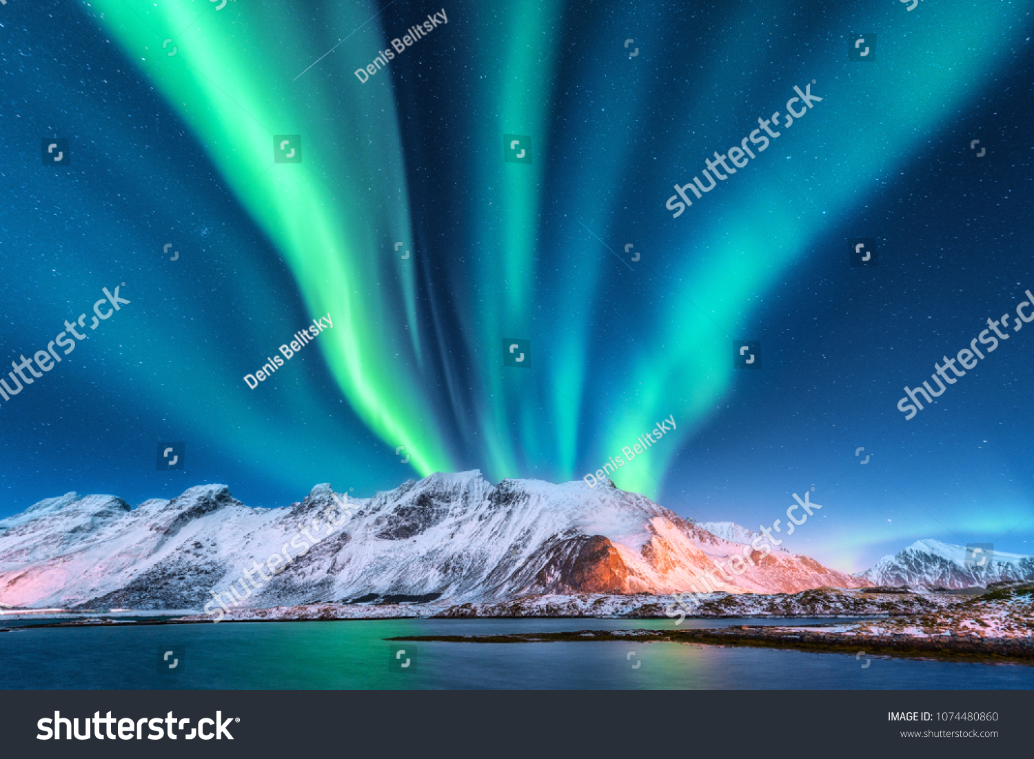Aurora borealis. Lofoten islands, Norway. Aurora. Green northern lights. Starry sky with polar lights. Night winter landscape with aurora, sea with sky reflection and snowy mountains.Nature background #1074480860
