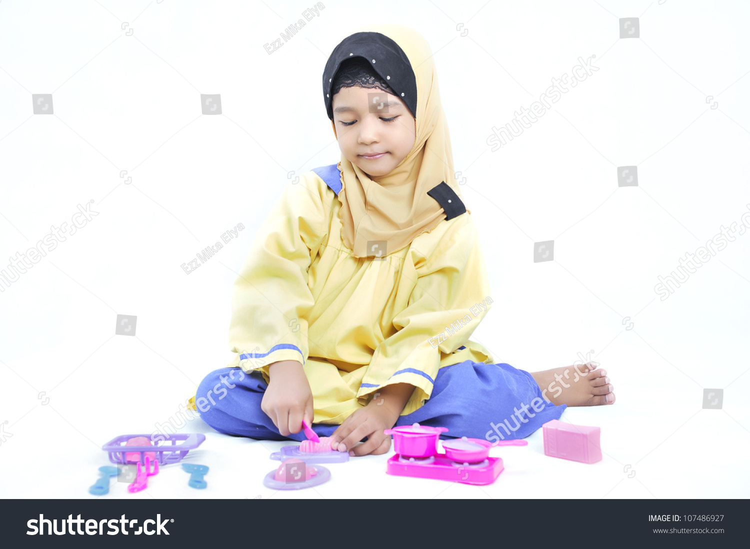 Happy young and cute muslim girl playing with a miniature cooking utensil toy in white