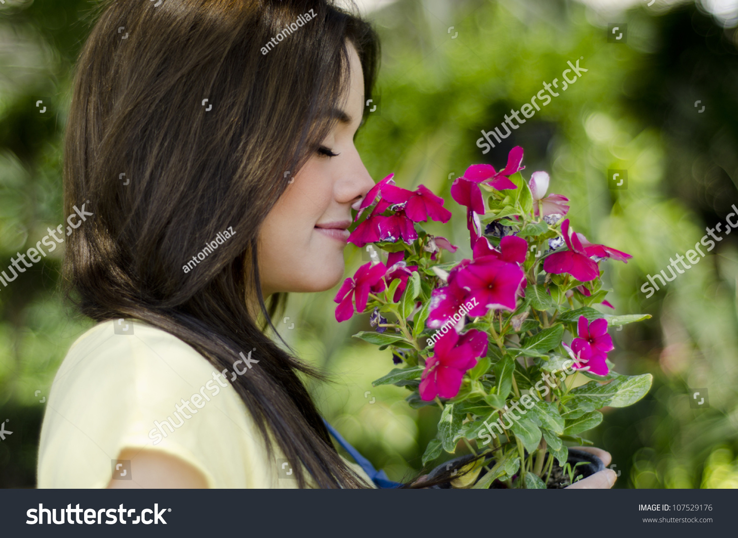 cute girl smelling flowers garden stock photo (royalty free