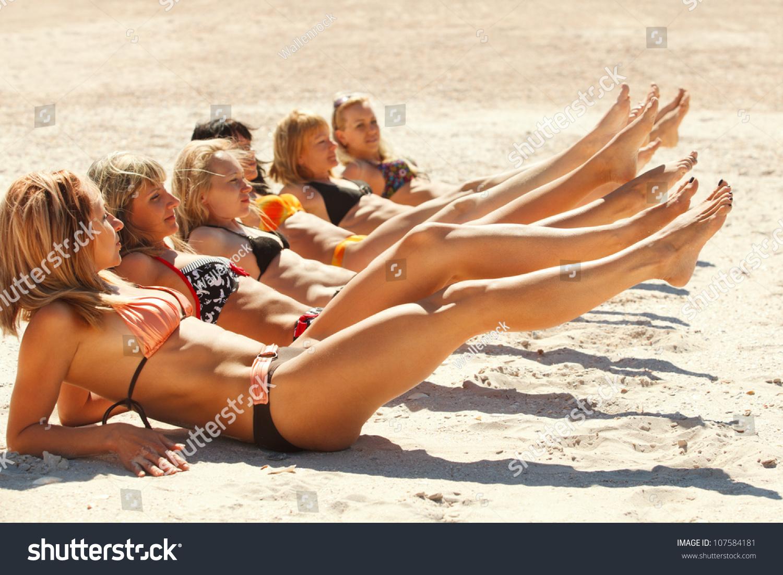 Photo Of Several Girls In Bikini Lying On Sandy Beach And Tanning ...