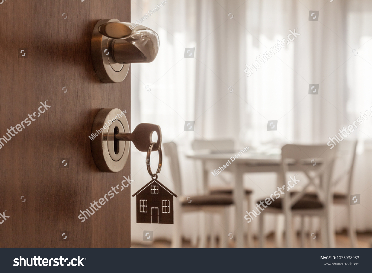 Open door to a new home. Door handle with key and home shaped keychain. Mortgage, investment, real estate, property and new home concept #1075938083