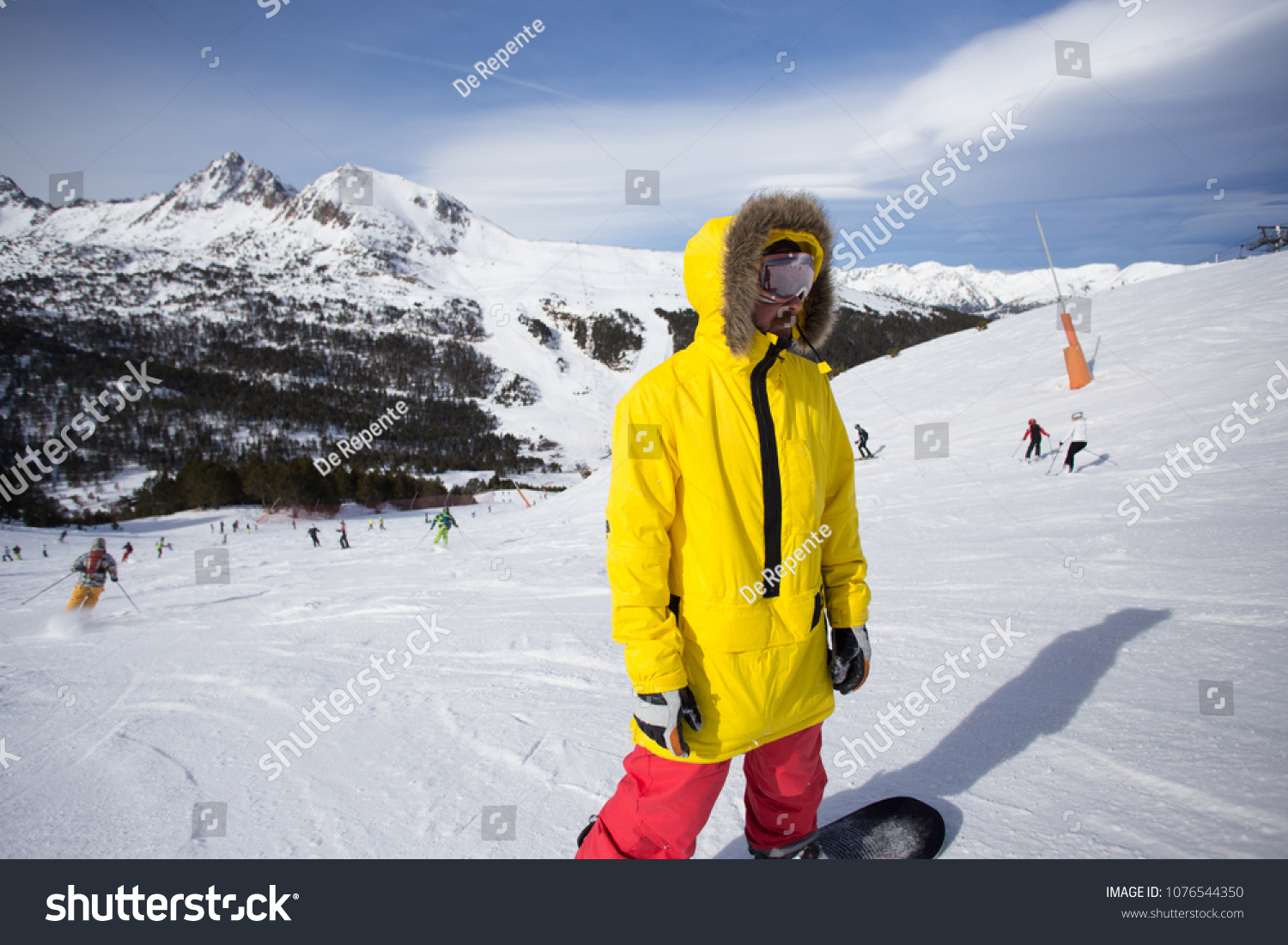 Cool and trendy young professional athlete or amateur snowboard rider  stands on top of hill or