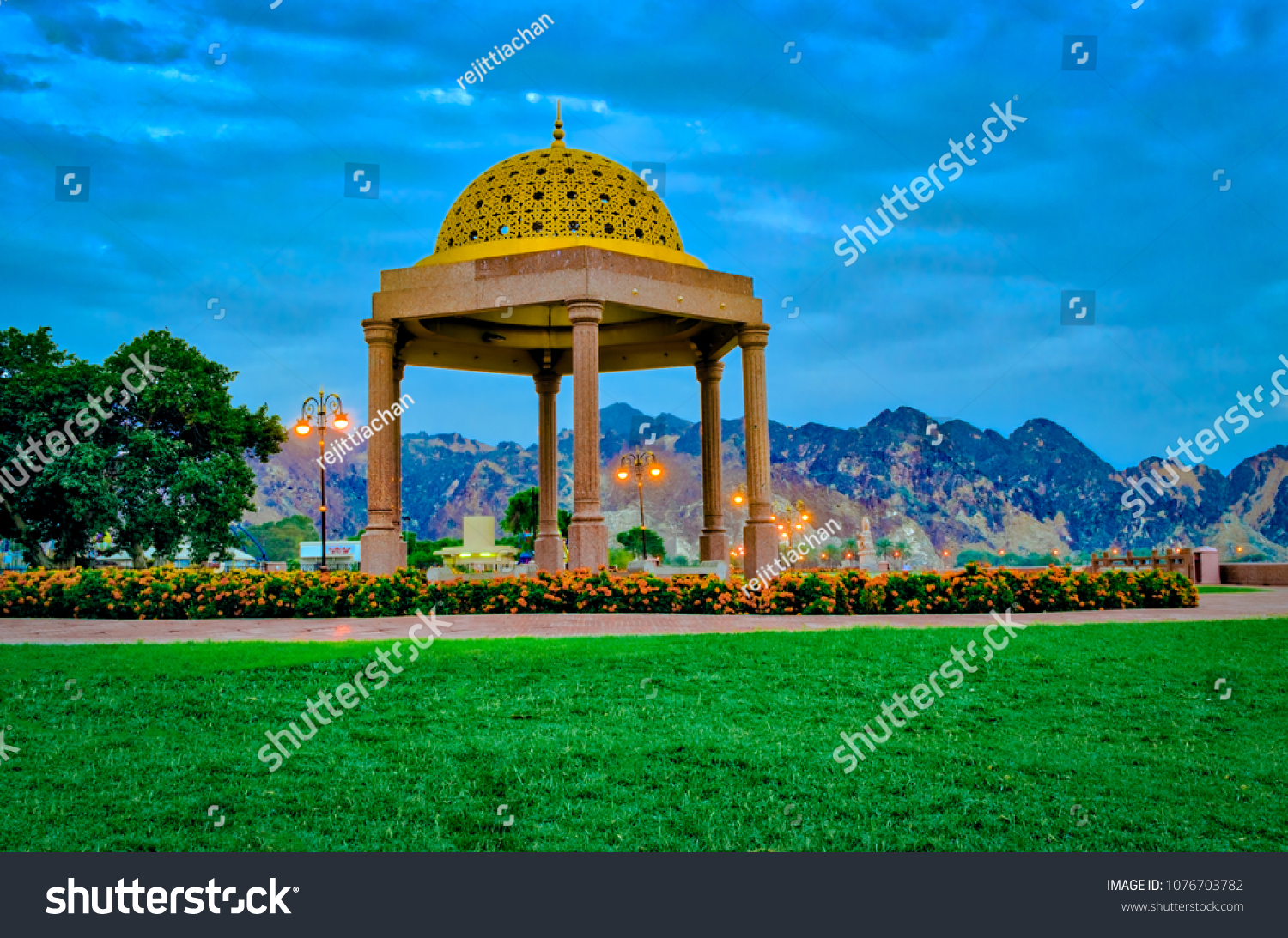 Golden Gazebo dome surrounded by green lawns, as a resting place for people in the Muttrah Corniche Park, Muscat, Oman.