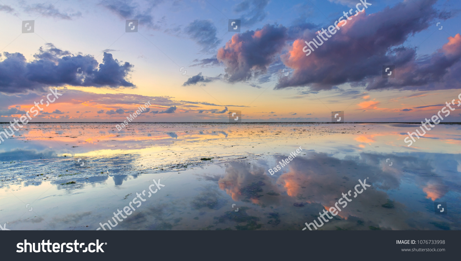 A calm and tranquil zen-like sunset at the beach with beautiful colours in pink and red with reflections on the water - Wadden sea, The Netherlands #1076733998