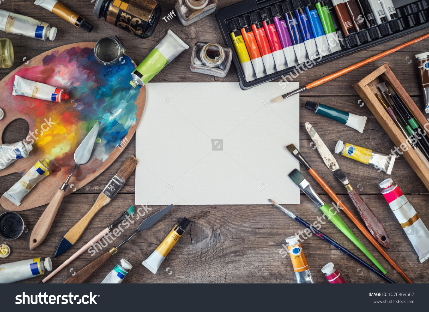 Set of artist accessories collection. Canvas, tube of oil paint, art brushes, palette knife lying on the wood table. Artist workshop background. #1076869667