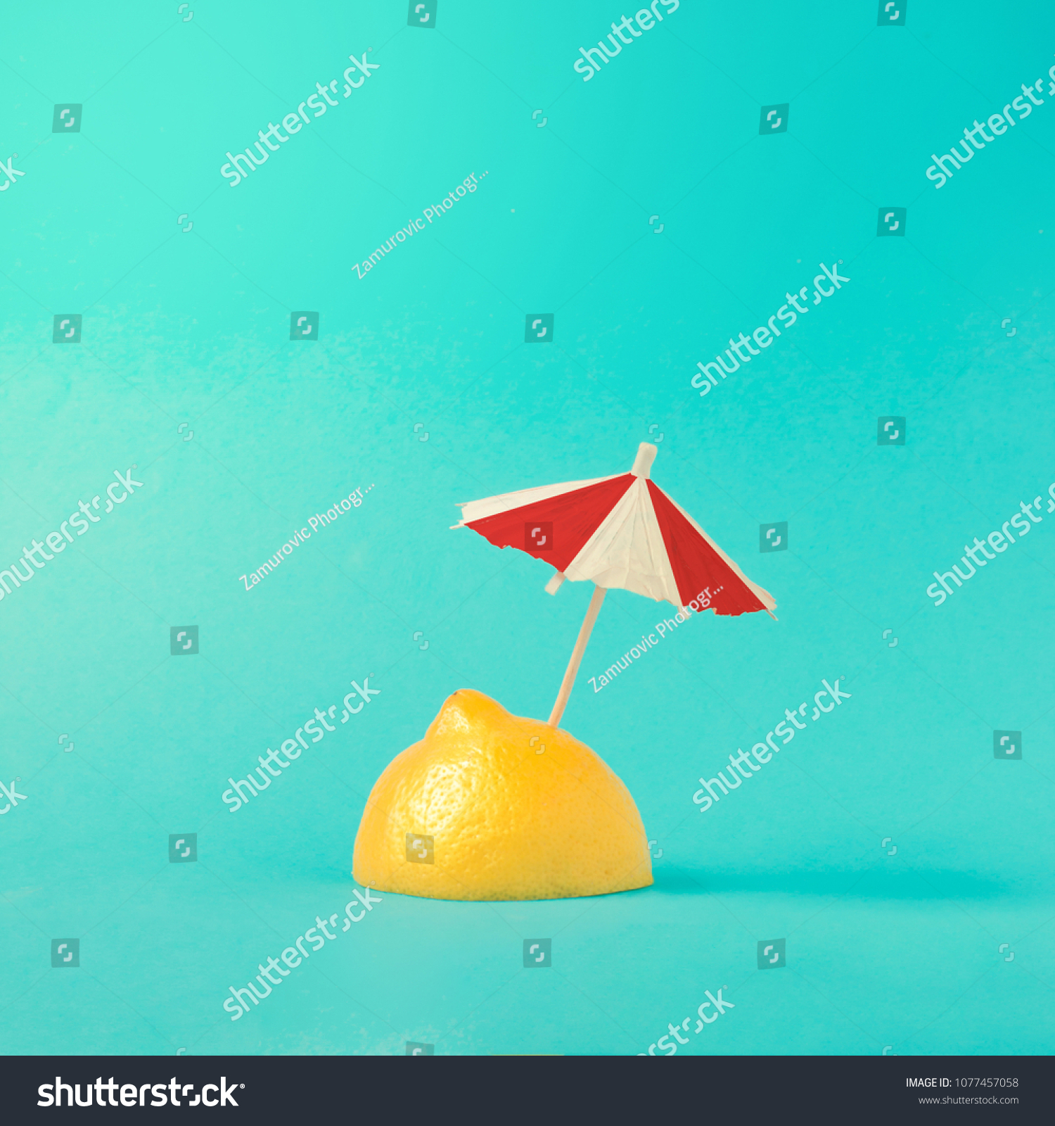 Tropical beach concept made of lemon and sun umbrella. Creative minimal summer idea. #1077457058