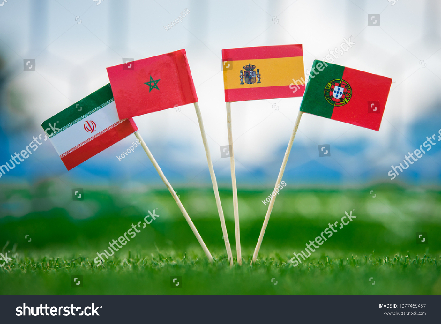 National Flags of Portugal, Spain, Morocco, IR Iran. Flags on green grass on football stadium. Group B.  #1077469457