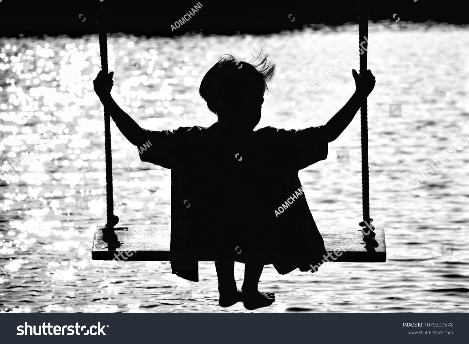 Black silhouette lonely little boy sitting on the wooden swing at river background holiday concept