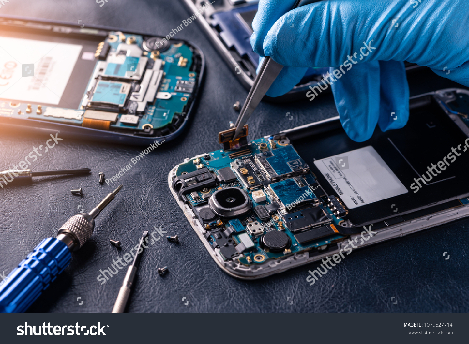 The asian technician repairing the smartphone's motherboard in the lab with copy space. the concept of computer hardware, mobile phone, electronic, repairing, upgrade and technology. #1079627714