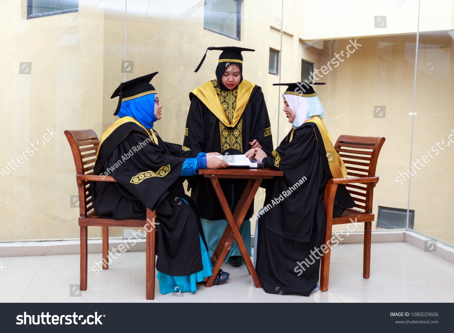 Three Women Of Student Discussing In Library With Graduation Dress Selective Focus Copy Space