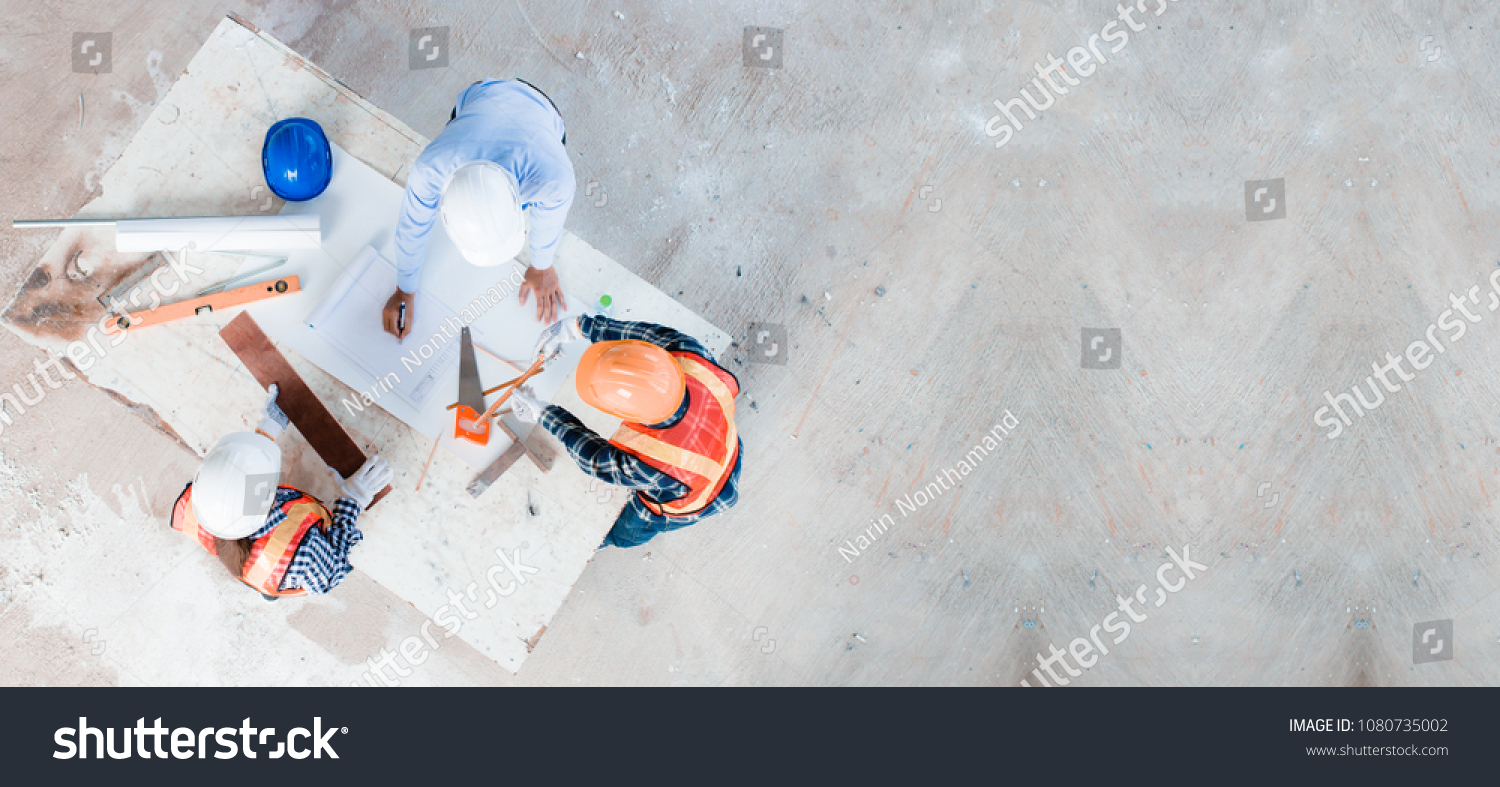 Team of young man and woman engineer and architects working, meeting, discussing,designing, planing, measuring layout of building blueprints in construction site floor at factory.top view & copy space #1080735002