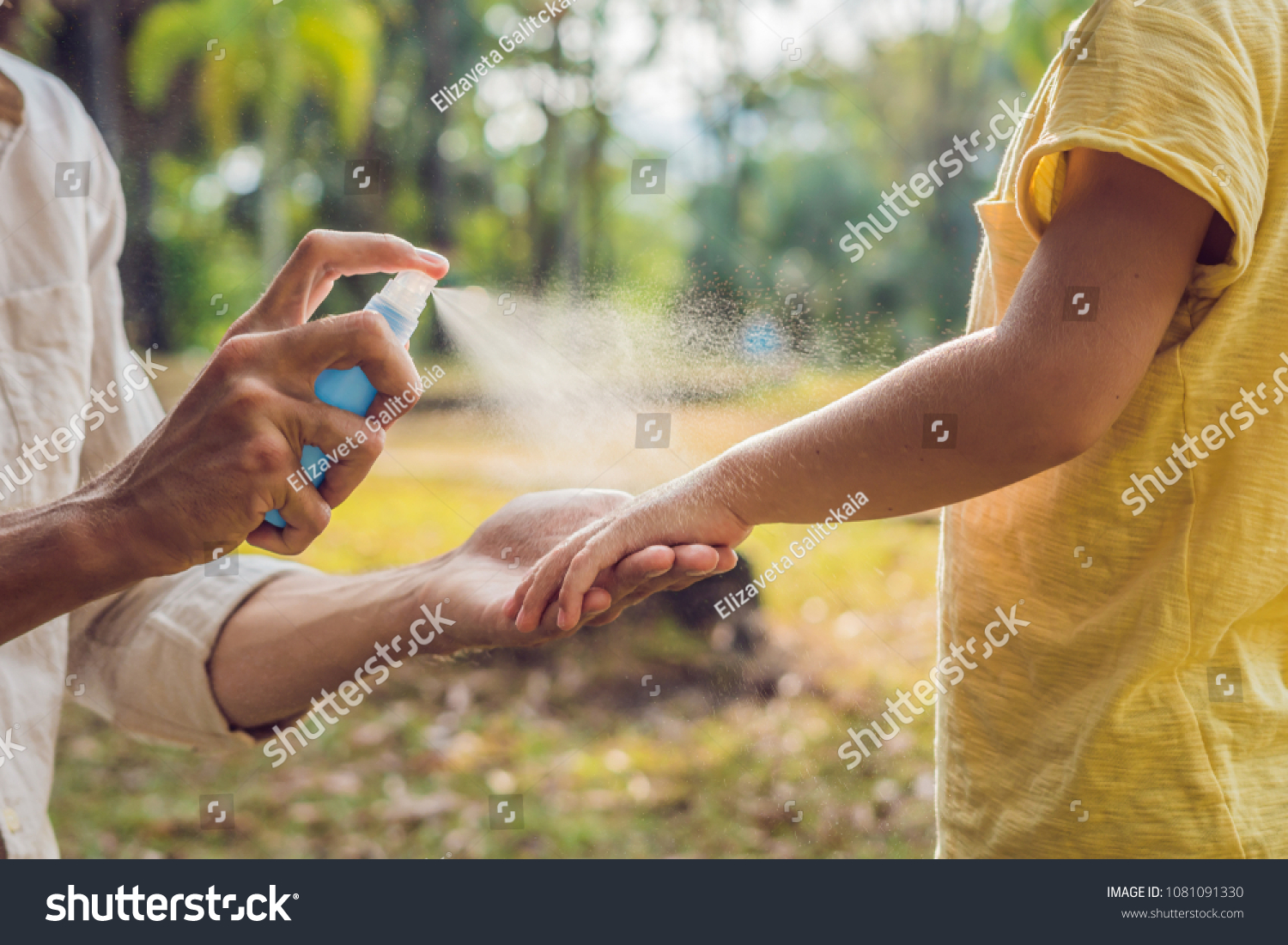 dad and son use mosquito spray.Spraying insect repellent on skin outdoor #1081091330