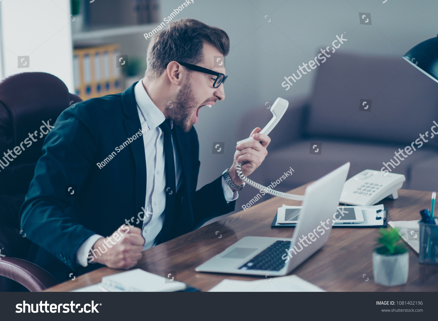 Corporate mad people yell authority tell speak with staff people person concept. Side profile view portrait of disappointed tired busy sad upset agent financier shouting on receiver in his hand #1081402196