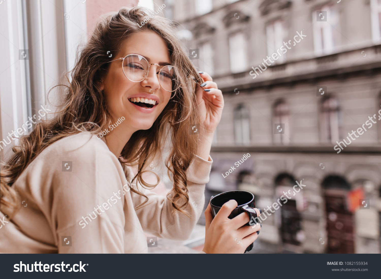 Close-up portrait of laughing brunette girl in beige sweater drinking coffee on city background. Lovable lady standing near window and looking at beautiful building with cup of tea. #1082155934