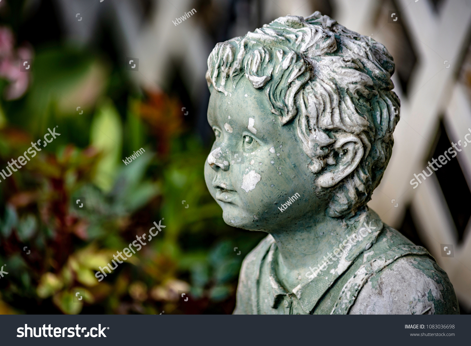 A Profile View Of A Decrepit Garden Statue Of A Little Boy Staring Off Into  The