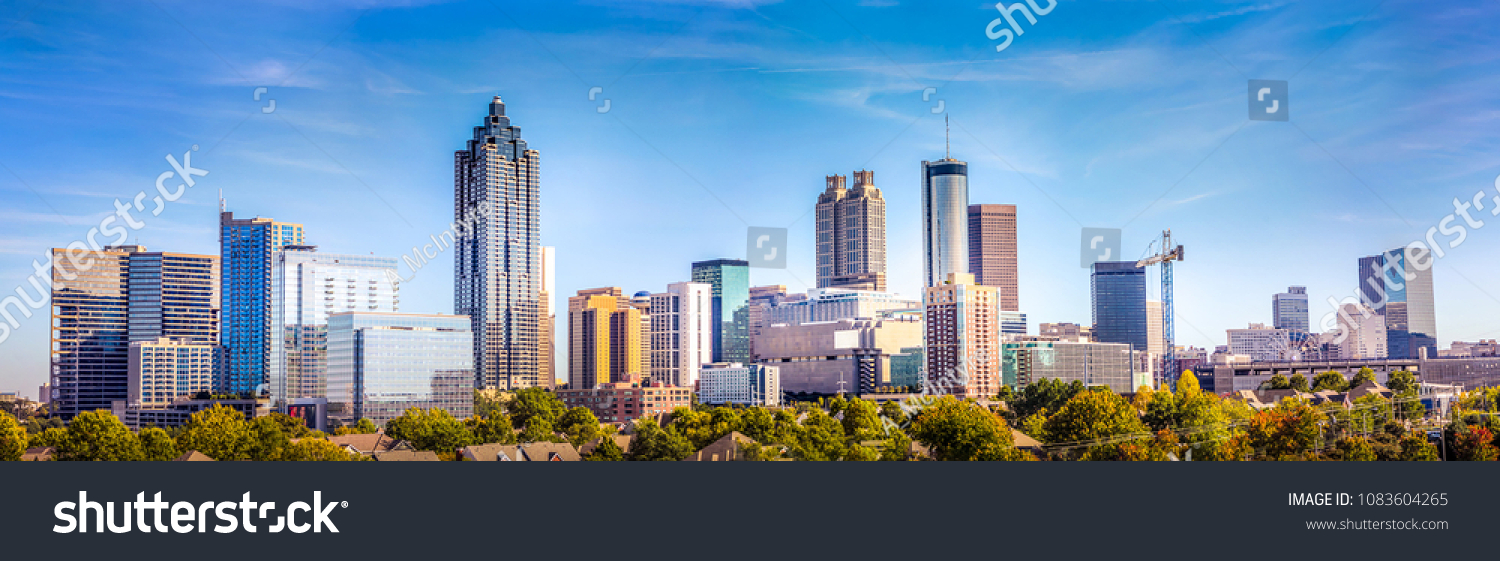 Downtown Atlanta Skyline showing several prominent buildings and hotels under a blue sky. #1083604265