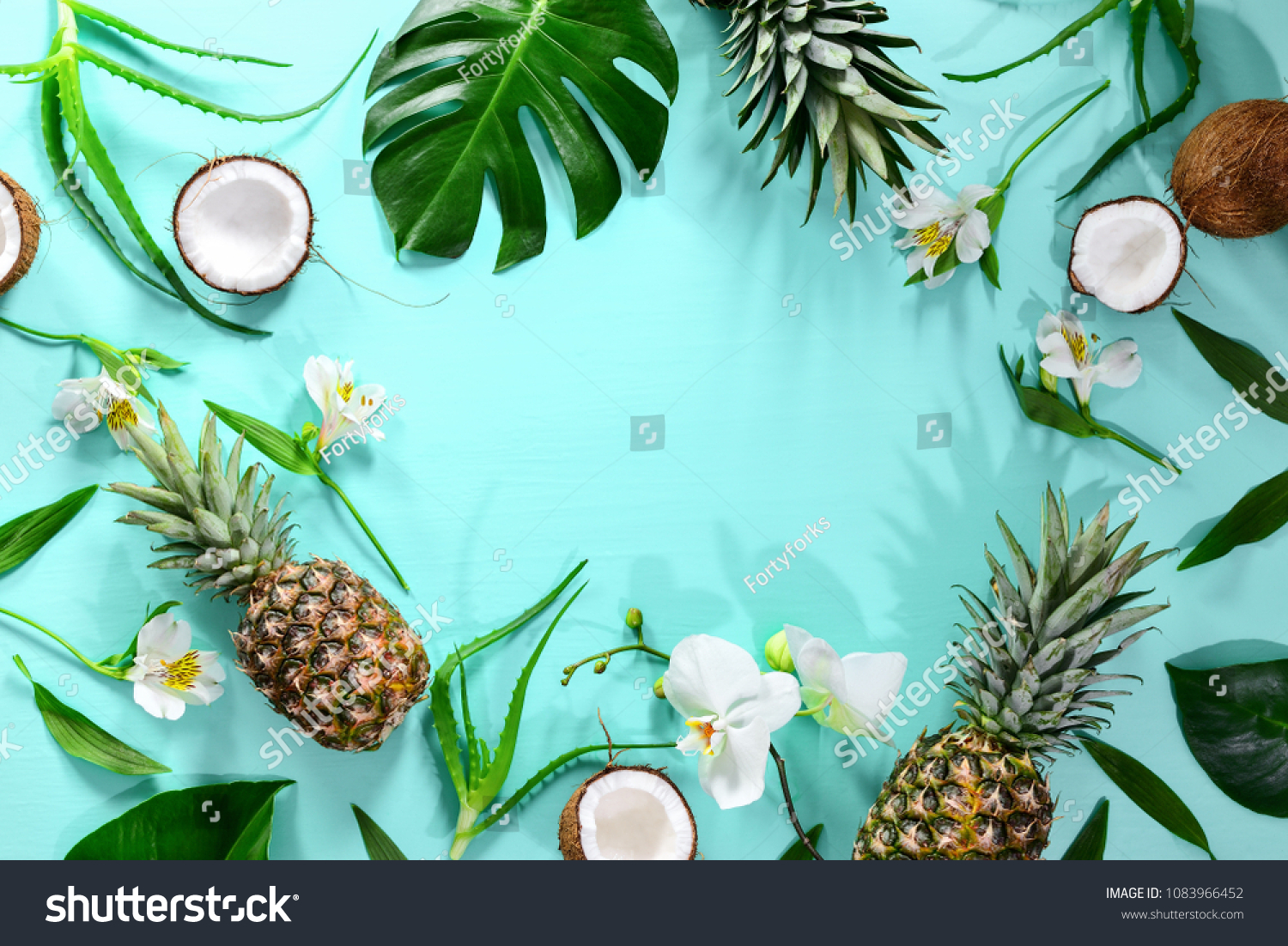 Summer tropical background with a space for a text, various fruits, green leaves and flowers arranged in a way that light shadows are fallen on the background surface, helping to keep some sum #1083966452