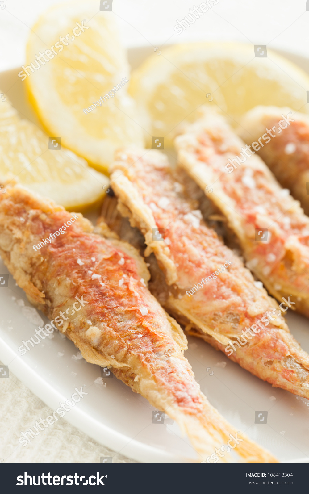 Fried red mullet fish with salt and lemon ready to eat for Eating mullet fish