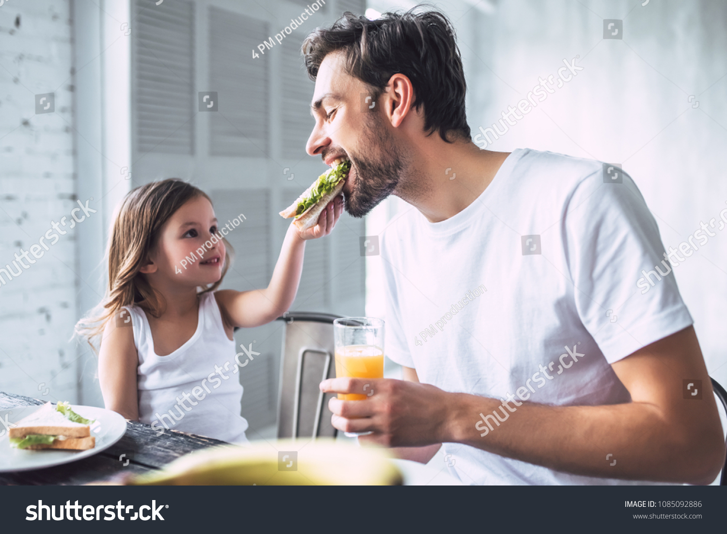 I love you, dad! Handsome young man at home with his little cute girl are having breakfast. Happy Father's Day! #1085092886