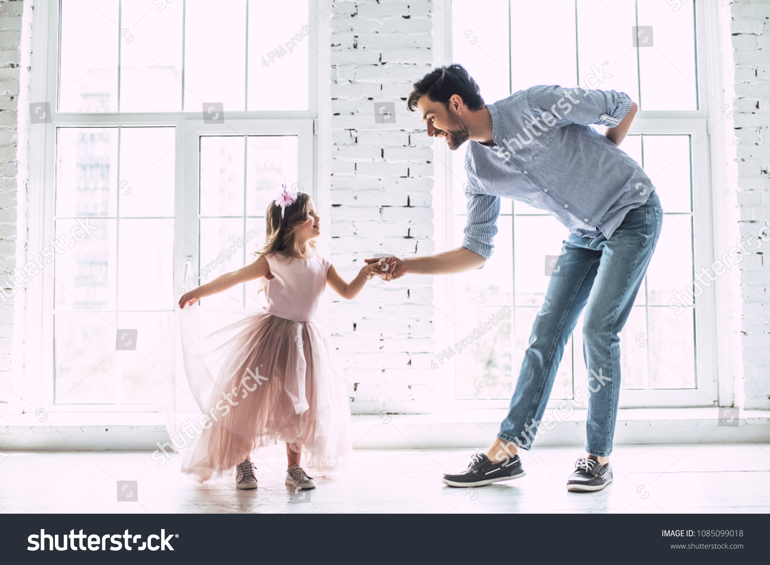 I love you, dad! Handsome young man is dancing at home with his little cute girl. Happy Father's Day! #1085099018