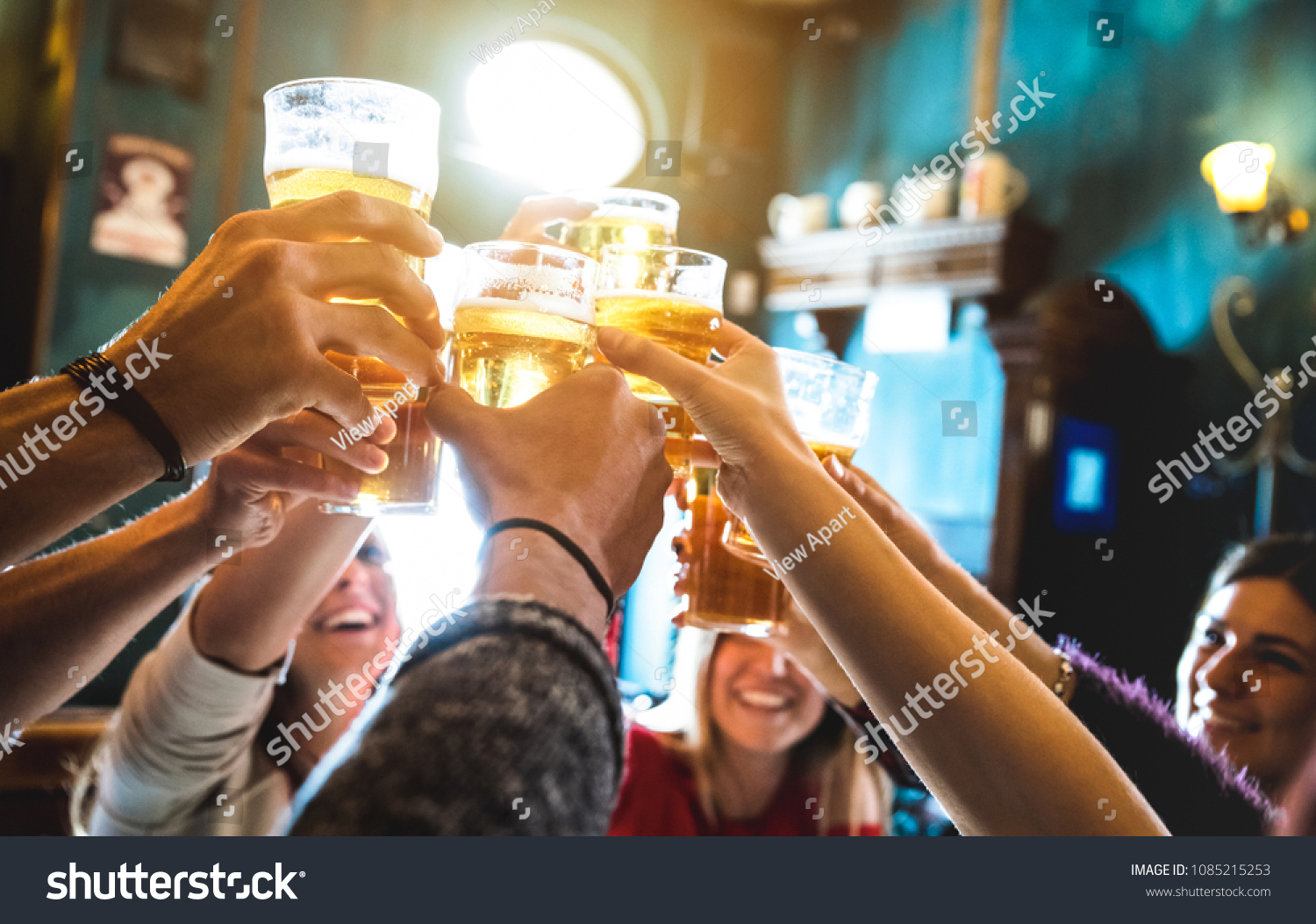Group of happy friends drinking and toasting beer at brewery bar restaurant - Friendship concept with young people having fun together at cool vintage pub - Focus on middle pint glass - High iso image #1085215253