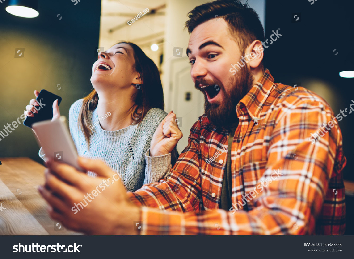 Excited male and female hipsters rejoice in winning an internet lottery made bets on website on modern smartphone.Happy couple in love celebrating victory in online competitions enjoying success #1085827388