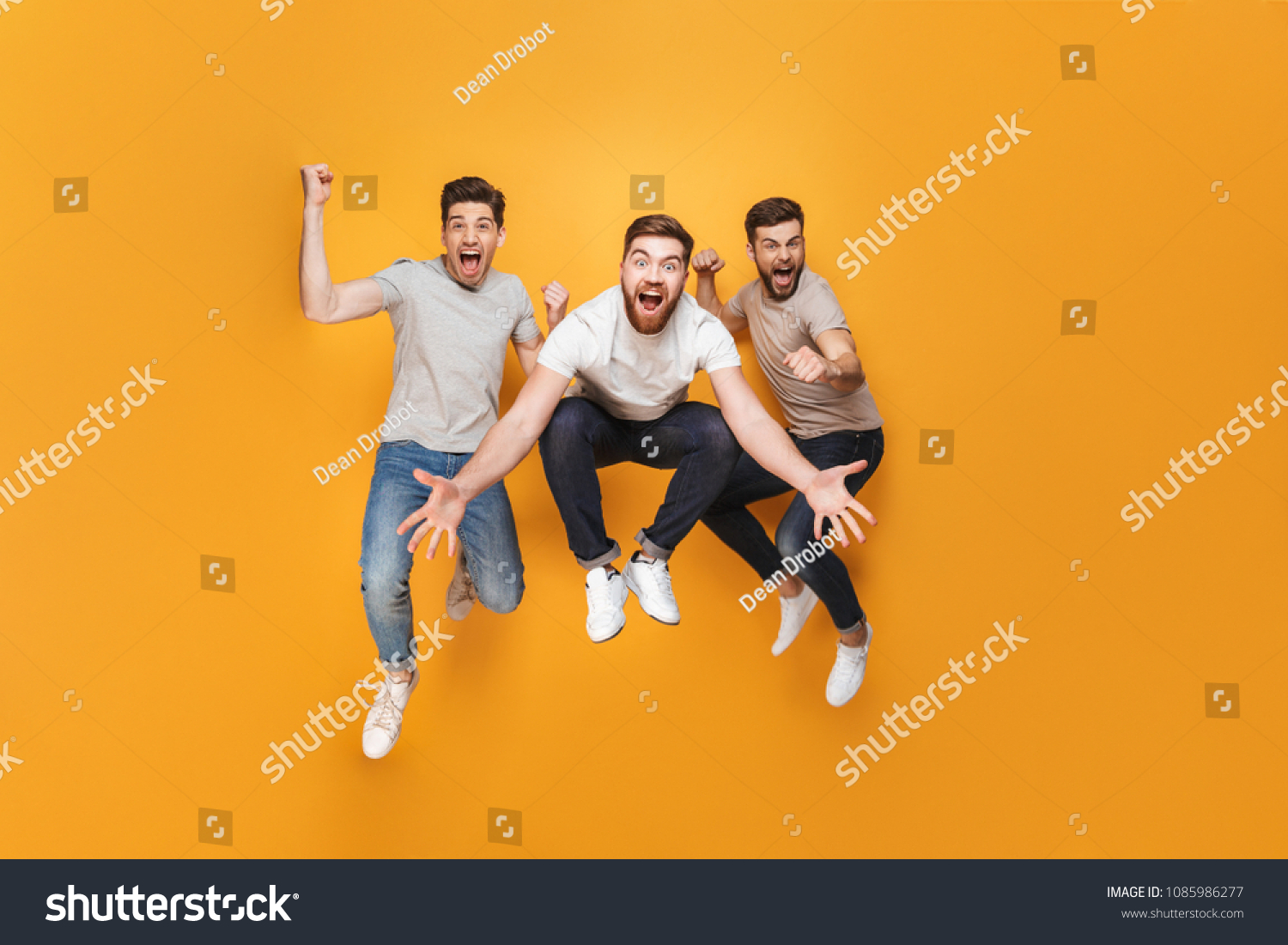 Three young excited men jumping together isolated over yellow background #1085986277 - 123PhotoFree.com