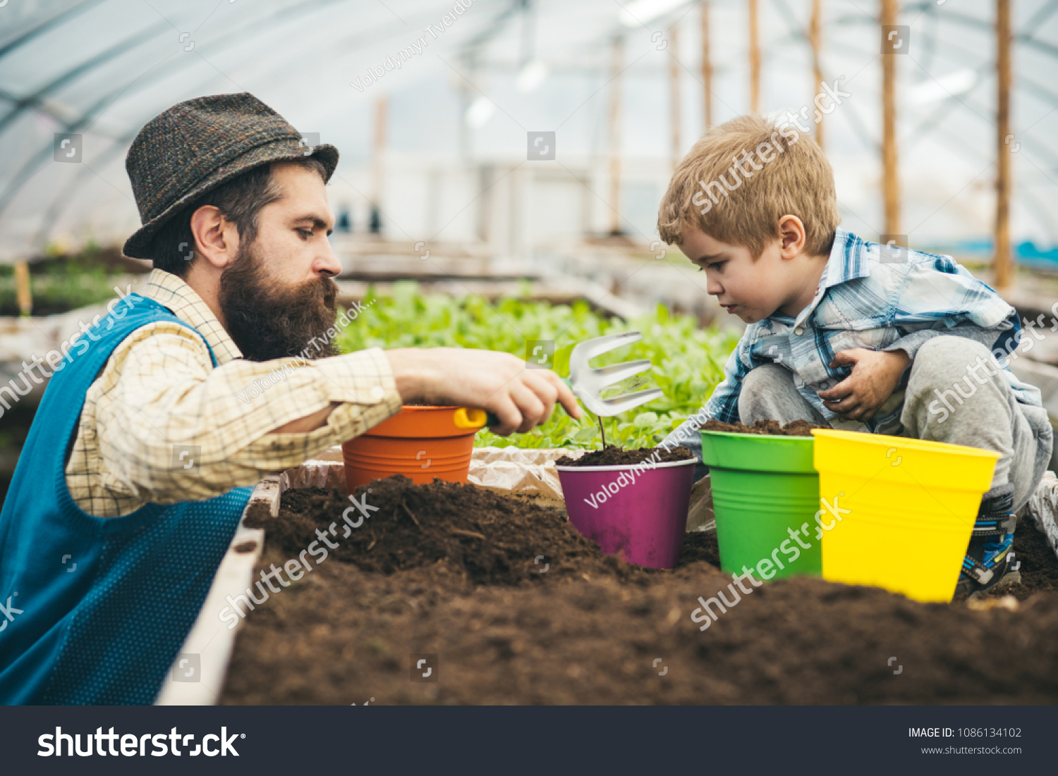 Side view father helping kid to plant flower with hand fork. Bearded man teaching his son gardening. Family and home education concepts. #1086134102