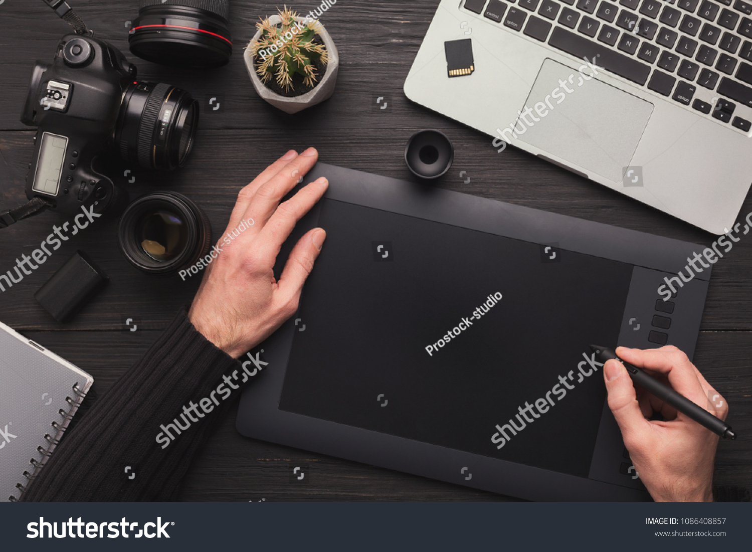 Top view on workplace of photographer. Creative designer hands working graphic tablet, photographic equipment on table #1086408857