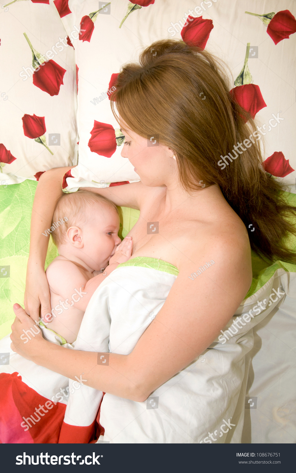Mother is breast feeding baby in bed Mother's love Bedding has a pattern of red roses